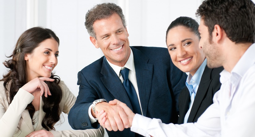 A medical doctor, in a white lab coat, shaking hands with a patient and an insurance agent.